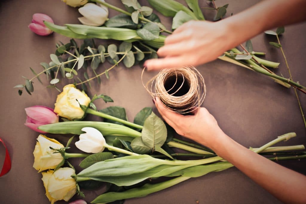 Florist arranging flowers using a recipe from a customer relationship management